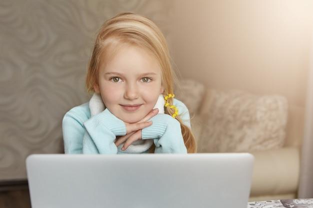Adorável aluna do primeiro ano com cabelo loiro preso em rabo de cavalo sentada em frente a um laptop aberto