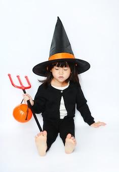 Adorável bebê bruxinha de halloween está sentado