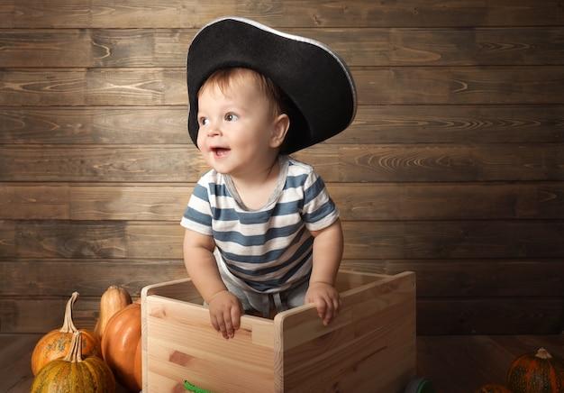 Adorável bebê com fantasia de pirata perto da parede de madeira. conceito de halloween