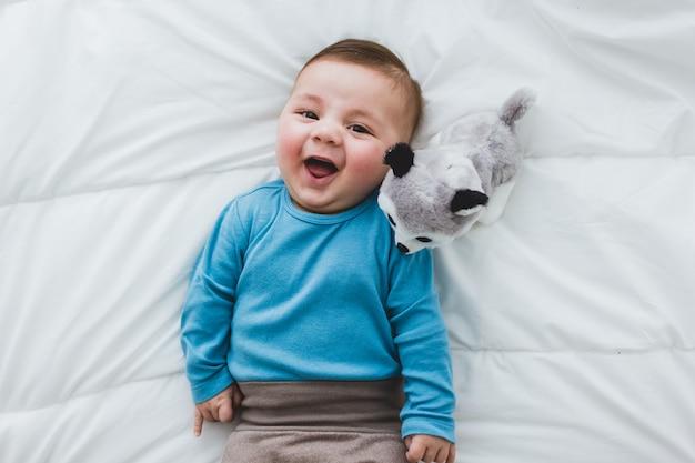 Adorável bebê com um cachorro de brinquedo ao lado