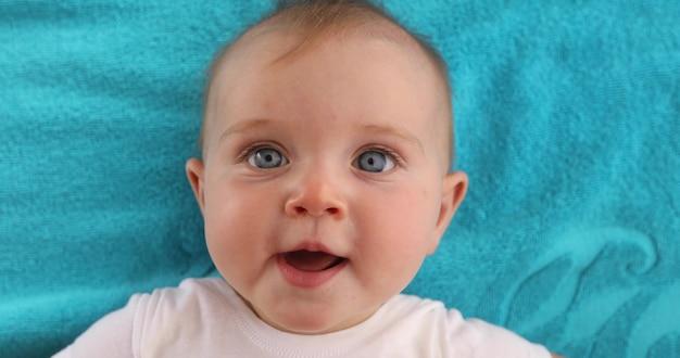 Adorável bebê de olhos azuis com a boca aberta, deitado na toalha azul e olhando para a câmera