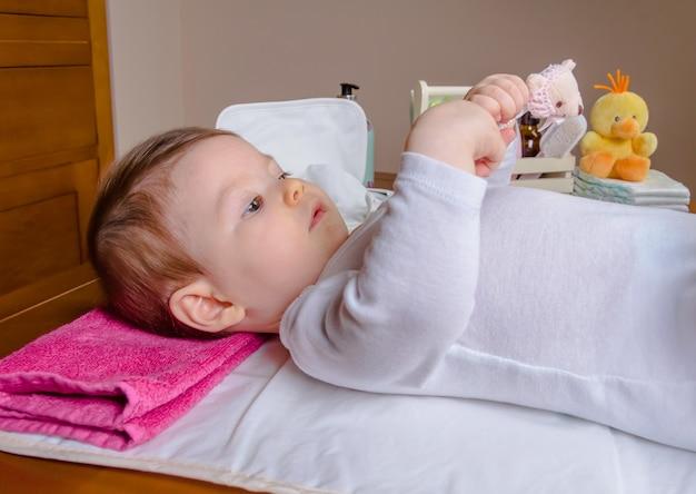 Adorável bebê deitado brincando com um pente de criança após a troca da fralda