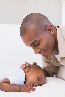Adorável bebê dormindo enquanto está sendo visto pelo pai