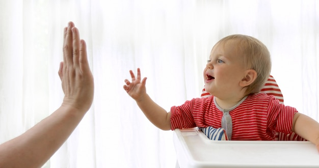 Adorável bebê feliz brincando com pai dentro de casa