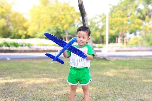Adorável bebê menino jogando um avião de brinquedo no jardim.