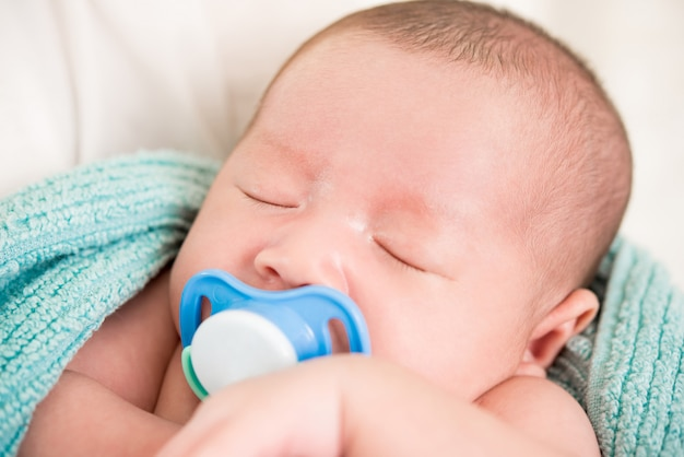 Adorável bebê recém-nascido dormindo com chupeta na boca