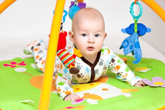 Adorável bebê se divertindo com brinquedos no tapete colorido.