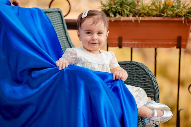 Adorável bebê sentado em uma cadeira de palha moderna com tecido azul e sorrindo