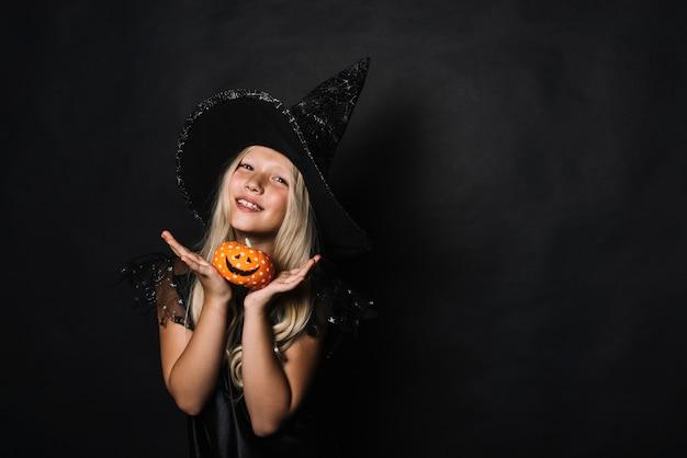 Adorável bruxa demonstrando jack-o-lanterna