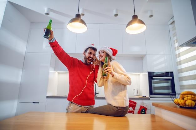 Adorável casal brincalhão ouvindo música sobre fones de ouvido, cantando, bebendo cerveja e se divertindo na cozinha