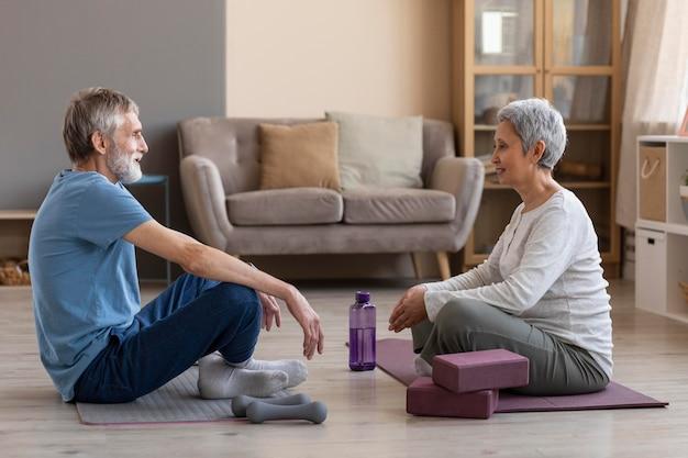 Adorável casal de idosos treinando em casa