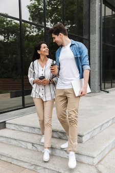 Adorável casal, homem e mulher em roupas casuais, bebendo café para viagem enquanto passeia pelas ruas da cidade
