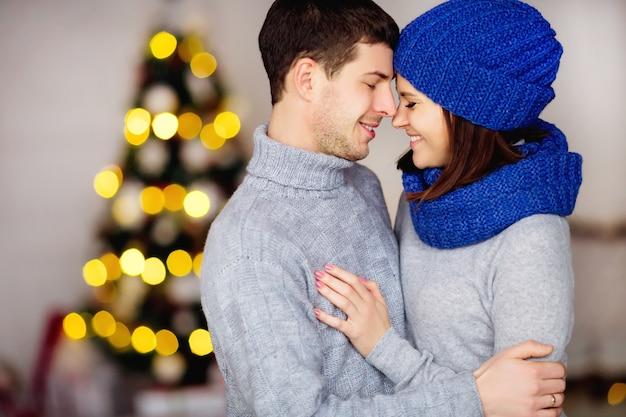 Adorável casal sonhador, doce e fofo se unindo em suéteres fofos de tricô, divirta-se