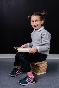 Adorável colegial animada com óculos e roupas casuais, sentada na pilha de livros enquanto lê um deles na frente da câmera contra o quadro