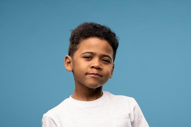 Adorável criança africana em idade elementar apertando os olhos no azul