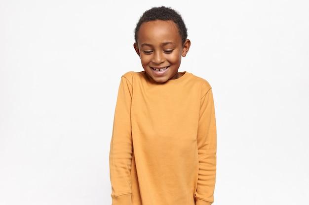 Adorável criança afro-americana com suéter amarelo olhando para baixo com timidez e expressão facial tímida