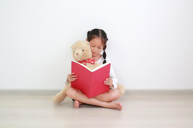 Adorável criança asiática lendo um livro com um ursinho de pelúcia sentado contra uma parede branca na sala.