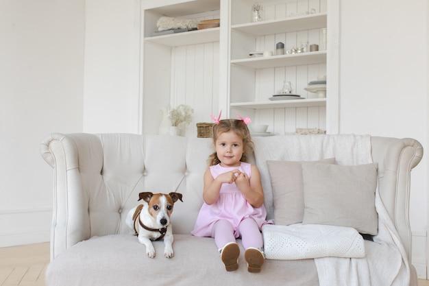 Adorável criança com cachorro no sofá