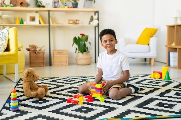 Adorável criança de etnia africana olhando para você sentado no tapete com decoração em preto e branco e jogando jogos de lazer na sala de estar