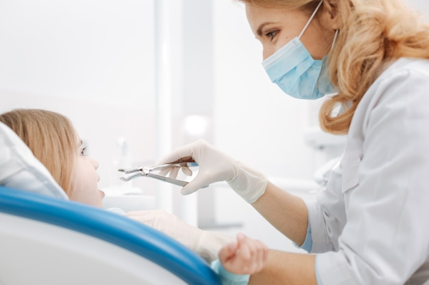 Adorável criança diligente e charmosa sentada na cadeira do dentista e esperando pacientemente enquanto o médico usa uma ferramenta especial para remover o dente