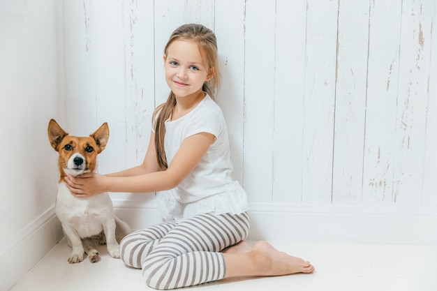 Adorável criança do sexo feminino pequena brinca com seu cachorro no quarto branco, sente-se no chão