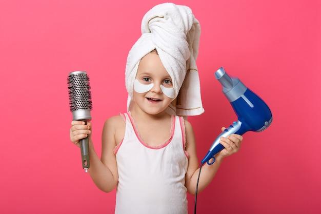 Adorável criança do sexo feminino segurando o secador de cabelo e pente nas mãos