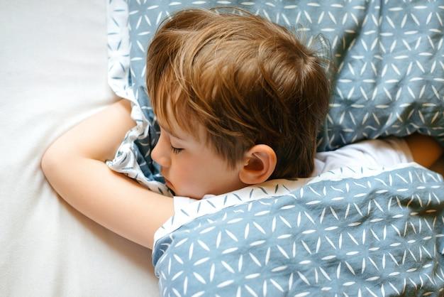 Adorável criança dormindo em sua cama