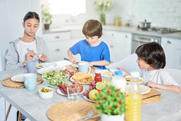 Adorável criança hispânica tomando café da manhã junto com seus irmãos. crianças desfrutando da refeição, sentadas à mesa na cozinha em casa. infância, conceito de cozinha latina