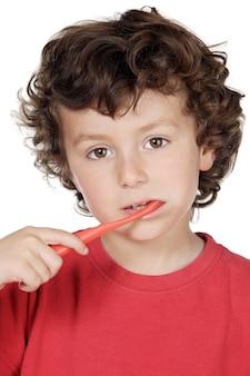Adorável criança limpando os dentes sobre fundo branco