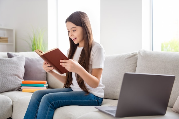 Adorável curiosa menina inteligente lendo um livro, relaxe dentro de casa