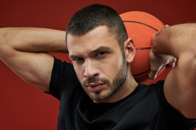 Adorável desportista de camisa preta a treinar com a bola no fundo vermelho