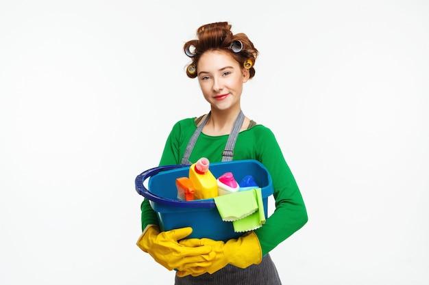 Adorável dona de casa posa segurando ferramentas de limpeza usando luvas amarelas