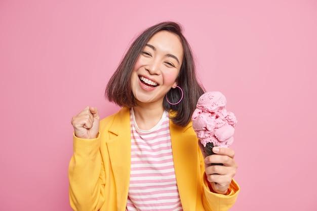 Adorável e alegre adolescente com aparência oriental, cabelo escuro inclina a cabeça fecha o punho come sorvete saboroso sorri amplamente se diverte curtindo o verão vestida com roupas elegantes isoladas na parede rosa