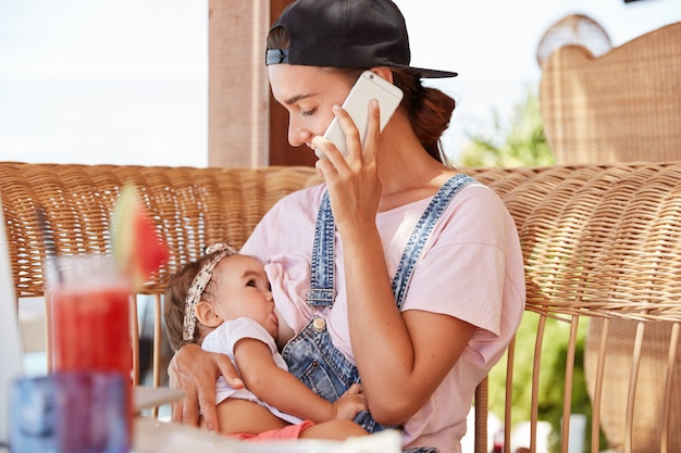 Adorável e alegre jovem mãe amamenta a filhinha, usa um boné preto da moda e um macacão jeans, fala com o marido no telefone inteligente, pede para comprar alguns produtos necessários, sente-se ao ar livre
