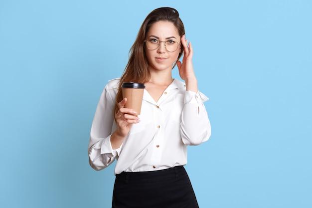 Adorável empresária de blusa branca e saia preta com café ou chá em copo de papel
