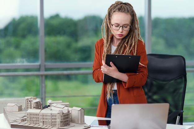 Adorável engenheira altamente qualificada fica perto de um modelo construído e fazendo anotações nos documentos técnicos