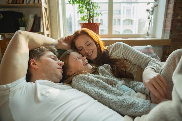 Adorável. família passando bons momentos juntos em casa, parece feliz e alegre. mãe, pai e filha se divertindo, deitados no sofá. união, conforto do lar, amor, conceito de relações.