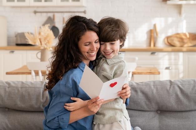 Adorável filho abraçando uma mãe sorridente segurando um cartão postal com um cartão de felicitações de aniversário no dia das mães