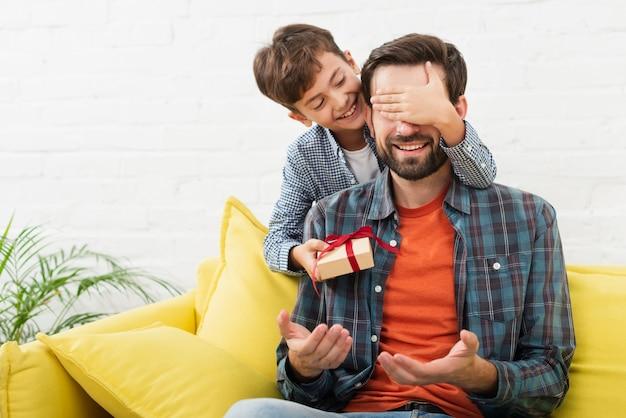 Adorável filho fazendo uma surpresa para o pai