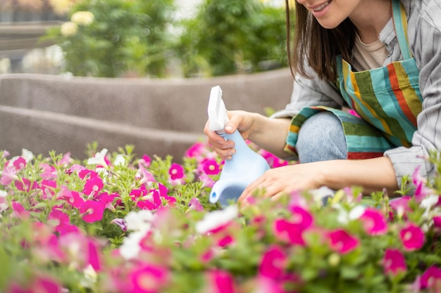 Adorável florista pulverizando água doce nas pétalas das folhas das flores trabalhando em uma estufa