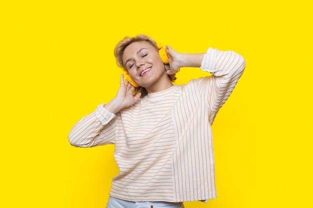 Adorável foto de perto de uma senhora loira que está ouvindo meditações e curtindo o tempo em uma parede amarela de estúdio
