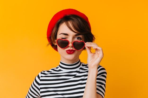Adorável francesa posando com óculos de sol em formato de coração