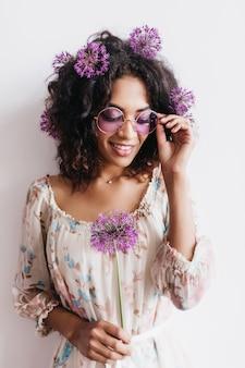 Adorável garota africana com penteado encaracolado segurando allium. senhora negra em óculos de sol posando com flores roxas.