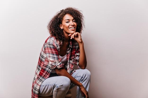 Adorável garota africana desfrutando de um ensaio fotográfico. mulher romântica de cabelos curtos em jeans que expressa emoções positivas.