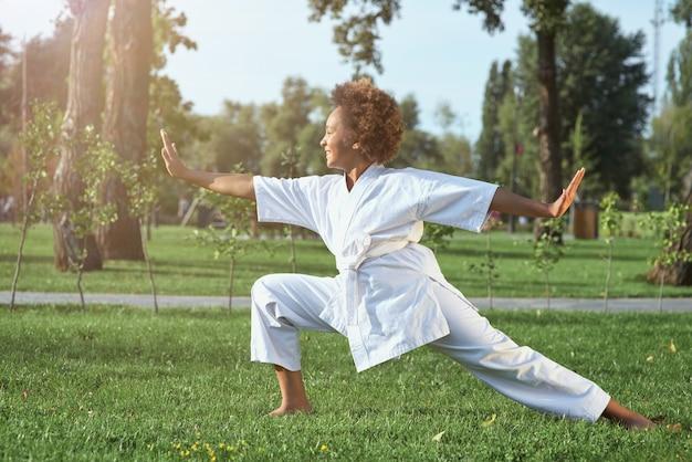 Adorável garota afro-americana praticando caratê em um dia ensolarado no parque