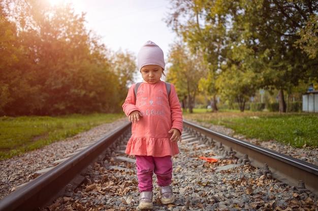 Adorável garota anda sozinha na ferrovia em um dia ensolarado de verão.