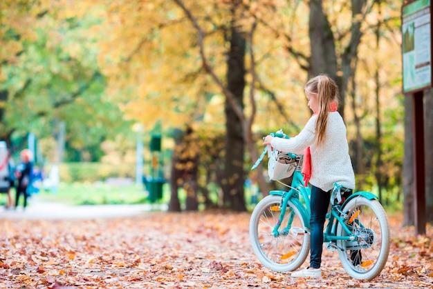 Adorável garota andando de bicicleta no lindo dia de outono ao ar livre