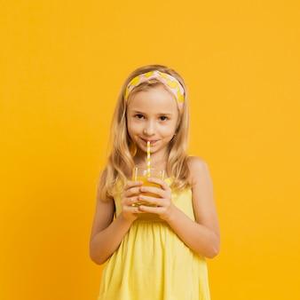 Adorável garota bebendo limonada com palha