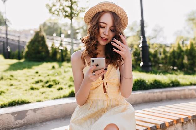 Adorável garota branca com manicure preta relaxando no lindo parque de verão. foto ao ar livre da graciosa modelo ruiva usando seu smartphone durante a sessão de fotos.