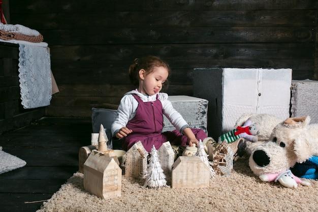 Adorável garota brincando com uma casa feita à mão
